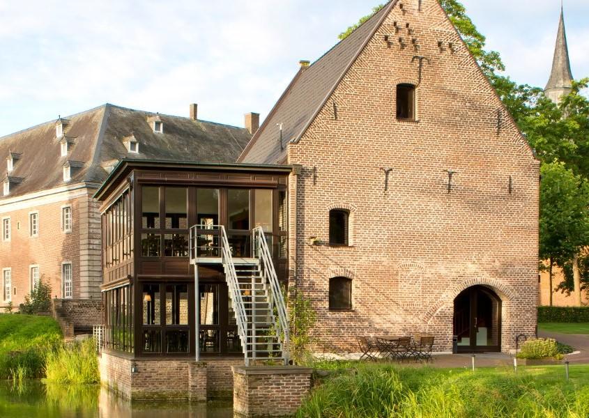 Historische Wassermühle mit modernem Anbau vor der Kulisse von Schloss Wissen